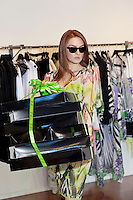 Young woman wearing sunglasses while carrying boxes in fashion boutique