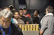 Nederland, The Netherlands, Rosmalen, 17-9-2015In de evenementenhal van het autotron worden maximaal 400 vluchtelingen opgevangen, veelal afkomstig uit Syrië of Eritrea. In deze noodopvang wachten zij op doorstroming naar een azc en verdere afhandeling van hun asielaanvraag. De mensen krijgen een maaltijd uitgedeeld. Eten, voeding. Vrijwilligers helpen hierbij.In Holland the growing number of refugees forces the government to house them temporary and improvised in unused or empty buildings and halls. Often these are rented from private owners or real-estate firms such as this one.FOTO: FLIP FRANSSEN/ HH