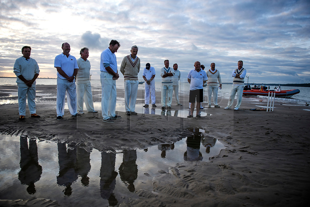 © Licensed to London News Pictures. 24/08/2017. Solent, UK. Players take part in a prayer before the match starts. Teams take part in the Brambles Bank Cricket Match in the middle of The Solent strait on August 24, 2017. The annual cricket match between the Royal Southern Yacht Club and The Island Sailing Club, takes place on a sandbank which appears for 30 minutes at lowest tide. The game lasts until the tide returns. Photo credit: Ben Cawthra/LNP