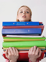 Female office worker carrying heavy binders close-up