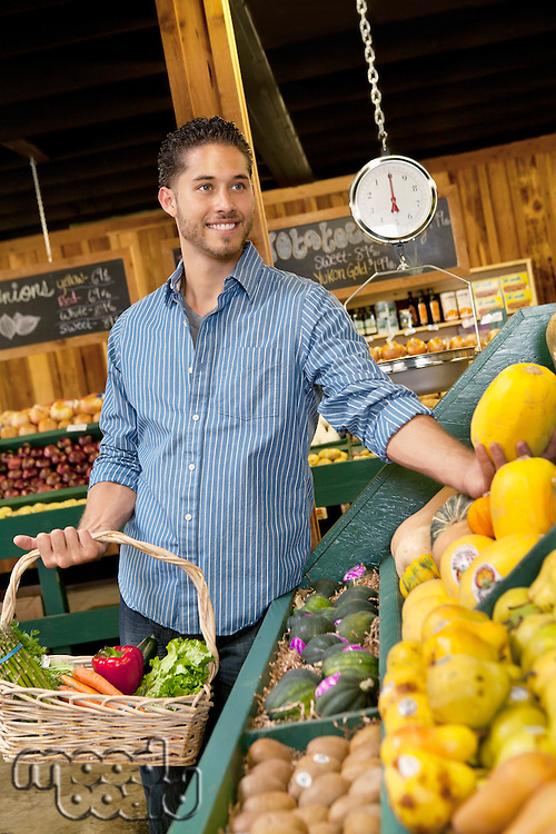 Handsome young man shopping for fruits in supermarket