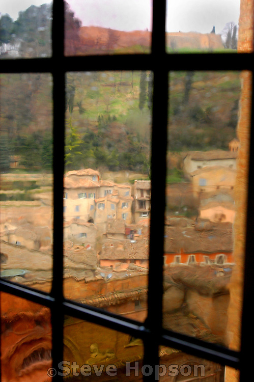 The view out the window of the Ducal Palazzo in Urbino Italy shows the renaissance town of Urbino and the Italian countryside of the Marches region through misshapen panes of old glass.