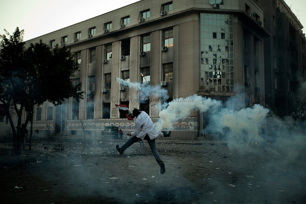 EGYPT, Cairo : An Egyptian protester throws a tear gas canister towards police during clashes with security forces near the Interior Ministry in Cairo, Egypt, Saturday, Feb. 4, 2012..