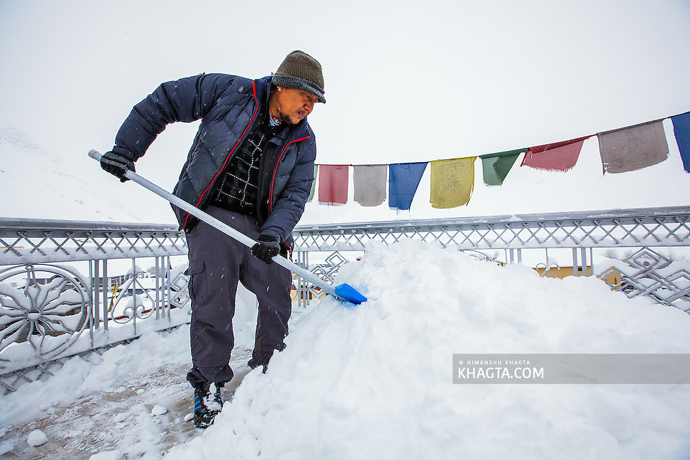 Tsering Bodh cleans snow from the roof top of his house. Spiti houses are made of mud and their roofs can't handle water, so it is a very important job in Spiti to clean the snow before it melts, even when its still snowing.
