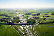 Nederland, Gelderland, Deil, 24-10-2013; knooppunt Deil, kruising A15 (vlnr) en A2, richting Den Bosch, Maas aan de horizin.  <br /> Betuweroute onder in beeld, vlnr parallel aan A15.<br /> Deil junction, main motorway A15 Rotterdam Harbour - Germany crossing A2 to the South. <br /> luchtfoto (toeslag op standaard tarieven);<br /> aerial photo (additional fee required);<br /> copyright foto/photo Siebe Swart.