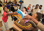 A volunteer distributes books to parents during the Hilliard Fall Festival, October 24, 2013. Free shoes were distributed to all the students and parents were able to sign up for services and receive books and backpacks for their children.