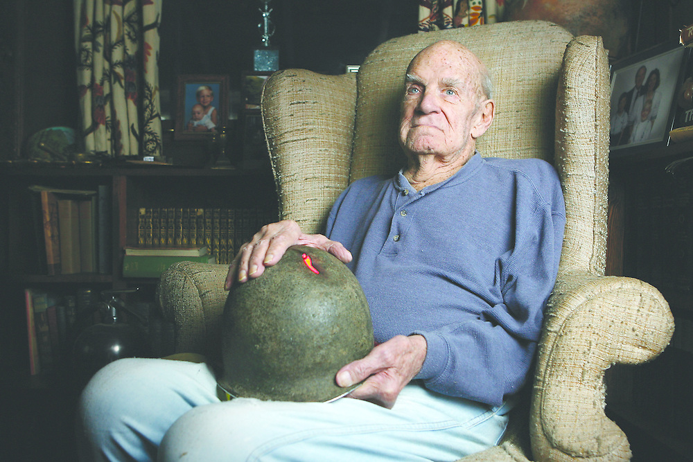 120707-Evergreen, CO-WWIIwallower-World War II Veteran Herb Wallower poses for a portrait with the helmet which saved his life Friday Dec. 7, 2007 at his home in Evergreen. Wallower served as a forward artillery observer during the war..Photo By Matthew Jonas/Evergreen Newspapers/Photo Editor