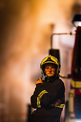 © Licensed to London News Pictures . 13/07/2013 . Manchester , UK . A fireman stands back as smoke billows from the scene . A fire fighter is dead and two 15 year old girls are under arrest on suspicion of manslaughter after a blaze in Manchester yesterday (Saturday 13th July) . More than 60 fire fighters tackled a blaze at Paul's Hair World on Oldham Street in Manchester City Centre late in to the night (Saturday 13th July 2013) . Twelve crews from four stations were deployed . Several streets in a block in the city centre are sealed off . Photo credit : Joel Goodman/LNP