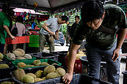 Tan Eow Chong's son, Tan Chee Wei (center), chooses durian fruits for his customers at Durian Kaki, a roadside fruit stall owned by Tan Eow Chong and his family in Bayan Lepas, Pulau Pinang, Malaysia on Sunday, June 16th, 2019. Tan Eow Chong is an award-winning durian farmer famed for his Musang King variety, and last year exported 1000 tons of the fruit to China from his family-run durian empire, expanding from an 80 acre farm to 1000 acres.  Photo by Suzanne Lee/PANOS for Los Angeles Times