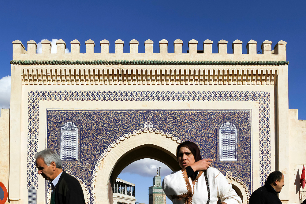 FEZ, MOROCCO - 17th NOVEMBER 2013 - People walking past Bab Boujloud / Bab Bou Jeloud - the Blue Gate - main entrance to the old Fez Medina, Middle Atlas Mountains, Morocco.
