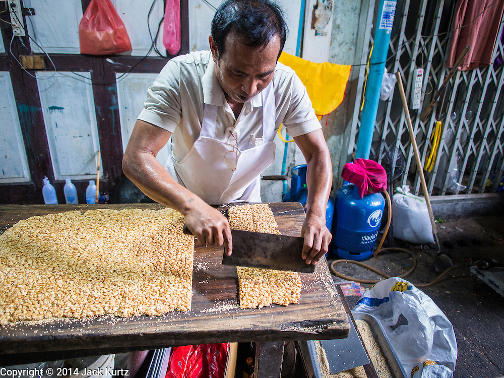 23 SEPTEMBER 2014 - BANGKOK, THAILAND:  A vendor makes home made Chinese peanut brittle on the first day of the Vegetarian Festival at the Chit Sia Ma Chinese shrine in Bangkok. The Vegetarian Festival is celebrated throughout Thailand. It is the Thai version of the The Nine Emperor Gods Festival, a nine-day Taoist celebration beginning on the eve of 9th lunar month of the Chinese calendar. During a period of nine days, those who are participating in the festival dress all in white and abstain from eating meat, poultry, seafood, and dairy products. Vendors and proprietors of restaurants indicate that vegetarian food is for sale by putting a yellow flag out with Thai characters for meatless written on it in red.   PHOTO BY JACK KURTZ
