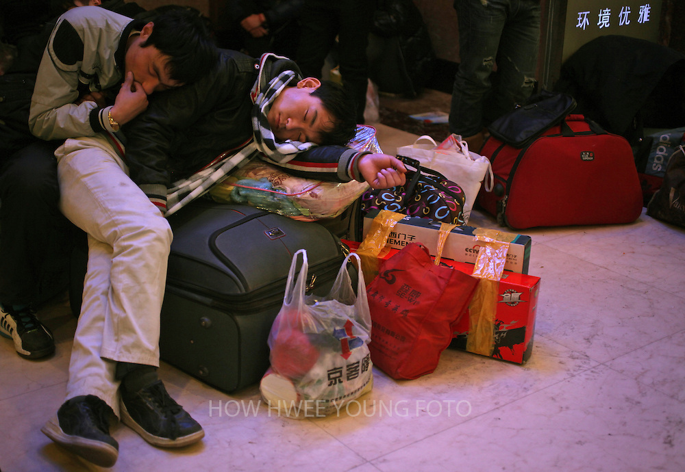epa03049723 Trainpassengers take a nap on their luggage as they are waiting for their train at a railway station in Beijing, China, 05 January 2012. China's railways are expected to carry an estimated 235 million passengers in the annual spring festival travel rush according to local media as migrant workers return to their hometowns to celebrate the Chinese lunar new year beginning on 23 January.  EPA/HOW HWEE YOUNG