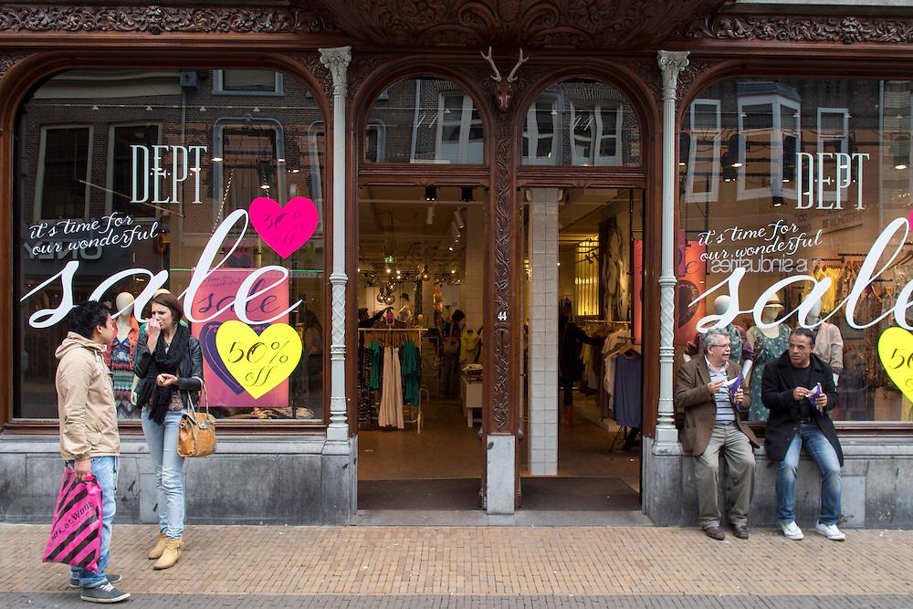 Buiten een modewinkel die uitverkoop houdt, wachten mensen.<br /> <br /> People are waiting outside a fashion store on sale.
