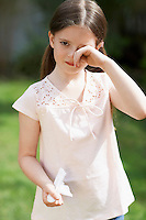 Little girl with cold rubbing eyes in backyard portrait