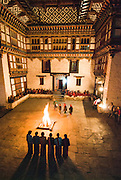 BHUTAN, EUNDU CHHOLING, winter palace of the first King Ugyen Wangchuck. There are 6 Bhutanese women singing in the palace courtyard, beside a wood fire at night.