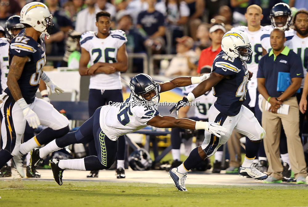 San Diego Chargers running back Branden Oliver (43) straight arms diving Seattle Seahawks rookie defensive back Ryan Murphy (36) as he runs with the ball after catching a 70 yard pass good for a third quarter touchdown that cuts the Seattle Seahawks lead to 13-12 during the 2015 NFL preseason football game against the Seattle Seahawks on Saturday, Aug. 29, 2015 in San Diego. The Seahawks won the game 16-15. (©Paul Anthony Spinelli)