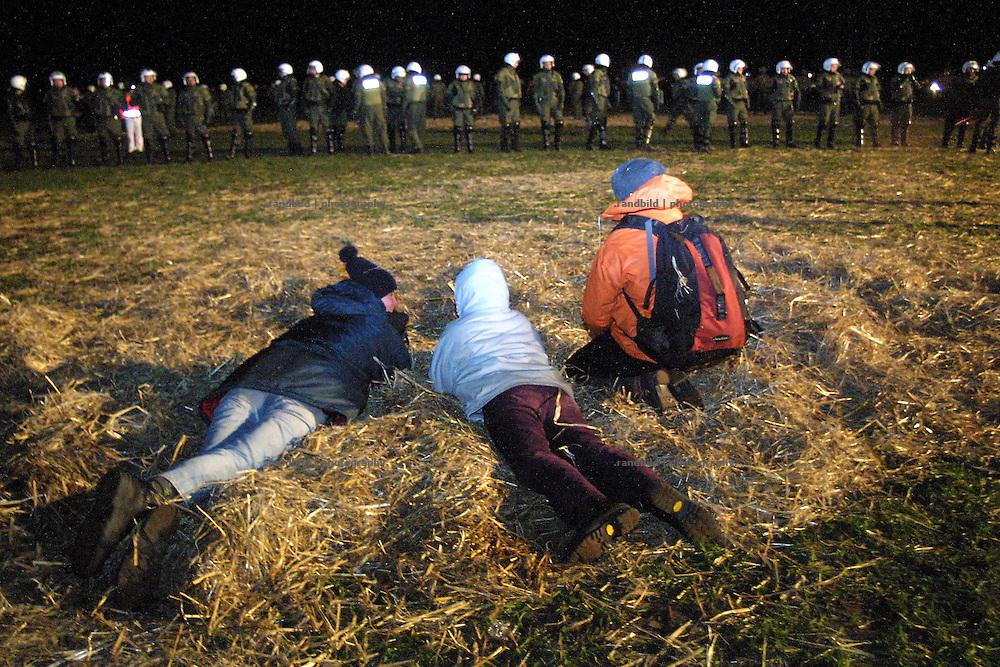 Drei Atomkraftgegner liegen nachts in der Nähe der von einer Polizeikette abgesperrten Castortransportstrecke in Dannenberg.