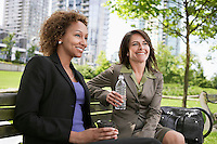 Two business women drinking on park bench