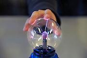 Nederland, Nijmegen, 11-2-2010Meisje aakt met de hand contact met een glazen bol waardoor elektrische ontlading plaatsvindt, nabootsing van bliksem.Foto: Flip Franssen/Hollandse Hoogte