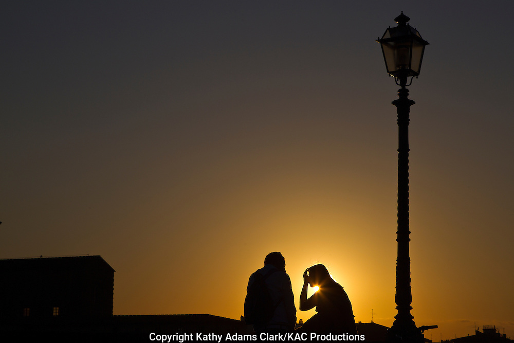 Couple talking at sunset on the Ponte alla Carraia, in Florence, Firenze, Italy.