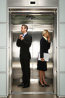 Businessman and Businesswoman checking their reflection in Office Elevator
