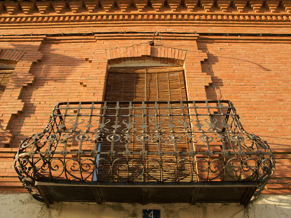 In Boadilla del camino, this fancy iron work balcony contrasted with the old red brick wall.