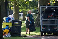 A worker in Queens Park loads rubbish bags onto her truck. Following the hottest May bank holiday weekend on record, park workers have their work cut out creating up the mess left behind by picnickers. London, May 08 2018.