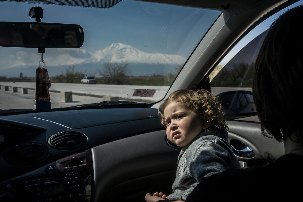 YEREVAN, ARMENIA - APRIL 17: Danil, a young passenger in a shared taxi to Stepanakert, rides in his mother's lap as Mount Ararat is visible on the horizon on February 21, 2015 in Yerevan, Armenia. Since signing a ceasefire in a war with Azerbaijan in 1994, Nagorno-Karabakh has functioned as a de facto part of Armenia, with hostilities along the line of contact between Nagorno-Karabakh and Azerbaijan occasionally flaring up and causing casualties. (Photo by Brendan Hoffman/Getty Images) *** Local Caption ***