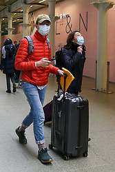 © Licensed to London News Pictures. 13/03/2020. London, UK. A couple wearing a face masks at St Pancras International station. 798 cases have been tested positive and ten patients have died from the virus in the UK. Photo credit: Dinendra Haria/LNP