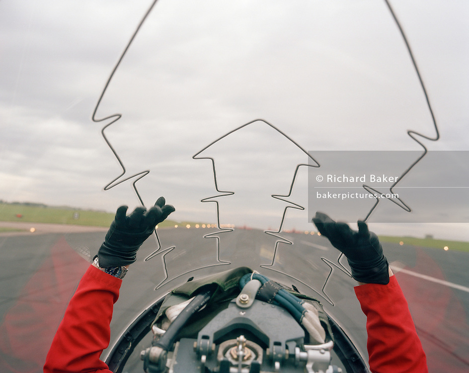 Seen from the cockpit of another Hawk of the elite 'Red Arrows', Britain's Royal Air Force aerobatic team before an In-Season Practice (ISP) training flight near their base at RAF Scampton. Seen through the explosive Plexiglass cockpit of a tenth plane, we see forward into deep blue sky as two sets of aerobatic pilots steer their machines from a crossover manoeuvre, their organic white smoke pouring from their jet pipes to emphasize their paths through the air. In front of a local crowd at the airfield the team work their way through a 25-minute series of display manoeuvres that are loved by thousands at summer air shows. After some time off, spare days like this are used to hone their manual aerobatic and piloting skills before re-joining the air show circuit. Since 1965 they've flown over 4,000 shows in 52 countries.