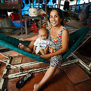 CAPTION: Nga with her grandchild at the family-run business, a cafe built on stilts over the river. Flooding incidents have damaged the floor during recent years, causing it to subside in several places. LOCATION: An Binh Ward, Can Tho, Vietnam. INDIVIDUAL(S) PHOTOGRAPHED: Tran Ngoc Thien Nhi, Phan Thi Nga.