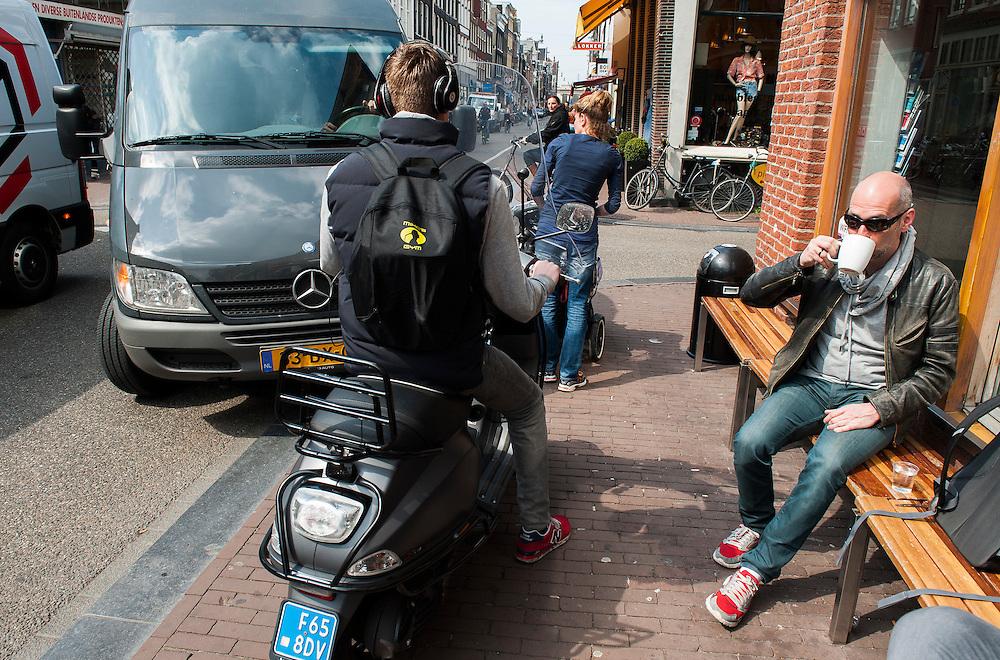 Nederland, Amsterdam, 22 april 2013<br /> Verkeer op de Haarlemmerdijk. Vanwege een lossende vrachtwagen staat het verkeer een beetje vast. Een bus en een scooter pakken de stoep mee, waar iemand rustig een kop koffie zit te drinken. Hij moet zijn benen intrekken.<br /> Foto(c): Michiel Wijnbergh