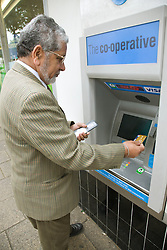 Older man withdrawing money from a cash machine,