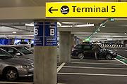 Man closes vehicle door and car park architecture at Heathrow's terminal 5.