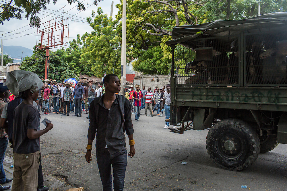 Anti-government protesters watch as a truck full of Haitian riot police passes by on Tuesday, December 16, 2014 in Port-au-Prince, Haiti. President Michel Martelly was elected in 2010 with great hope for reforms, but in the wake of slow recovery and parliamentary elections that are three years overdue, his popularity has suffered tremendously, forcing Prime Minister Laurent Lamothe to resign.