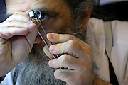 An Orthodox Jewish diamond dealer examines one of his many diamonds at a Hatton garden workshop, London.  Hatton Garden is the diamond centre of London.
