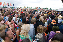 Crowd of people listening to a band on stage at WOMAD (World of Music; Arts and Dance) Festival; Charlton Park; Malmesbury; 2007,