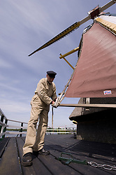 """Jaap Bes is the head volunteer miller at the De Ster Snuff and Spice mill in Rotterdam, The Netherlands. Bes stands on the """"Stage"""", a platform midway up the windmill's structure, and adjusts the sails attached to the mills' """"wings."""" Much like the sails on a boat, the tension of the mills' sails can be adjusted to produce the desired operating speed of the mill. (Photo © Jock Fistick)"""
