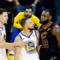OAKLAND, CA - MAY 31: Stephen Curry #30 of the Golden State Warriors talks to LeBron James #23 of the Cleveland Cavaliers next to Klay Thompson #11 of the Golden State Warriors in Game One of the 2018 NBA Finals won 124-114 in OT by the Golden State Warriors over the Cleveland Cavaliers at the Oracle Arena on May 31, 2018 in Oakland, California. NOTE TO USER: User expressly acknowledges and agrees that, by downloading and or using this photograph, User is consenting to the terms and conditions of the Getty Images License Agreement. Mandatory Copyright Notice: Copyright 2018 NBAE (Photo by Chris Elise/NBAE via Getty Images)