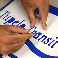 Jake Logan, Sign Tech with the Tupelo Public Works Department, weeds the vinyl on one of the new Tupelo Transit and Bus Stop sign decals Thursday afternooon at the Tupelo Public Works Department.
