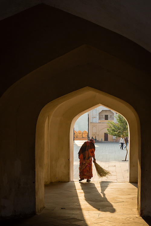 A woman sweeps an archway on the courtyard of Amber Palace.