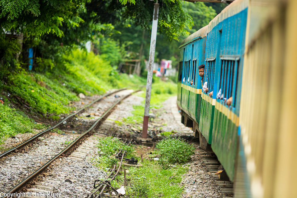 05 JUNE 2014 - YANGON, YANGON REGION, MYANMAR: The Yangon Circular Train rolls through the countryside north of Yangon. The Yangon Circular Train is a commuter train that circles Yangon, Myanmar (Rangoon, Burma). The train is 45 kilometers long, makes 38 stops and takes about three hours to make a loop of the city.     PHOTO BY JACK KURTZ