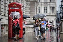 © Licensed to London News Pictures. 26/07/2019. London, UK. Members of the public brave wet and grey conditions in Westminster, central London as the capital is deluged with rain, following a week that saw the UK experience record temperatures for July. Photo credit: Ben Cawthra/LNP