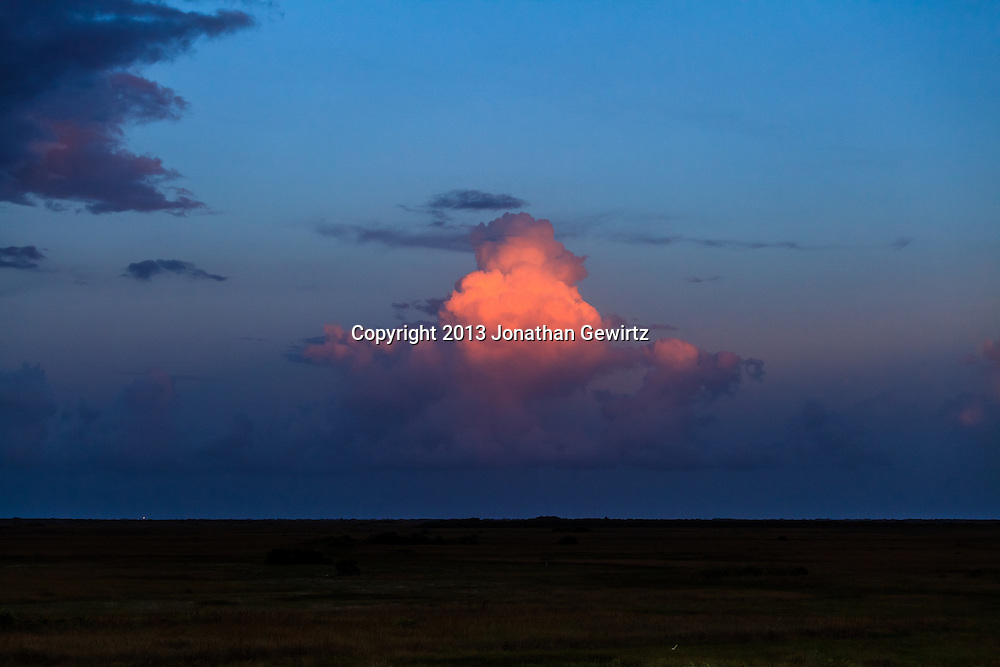 The last rays of the setting sun illuminate towering cumulus clouds over sawgrass prairie in the Shark Valley section of Everglades National Park, Florida. <br />