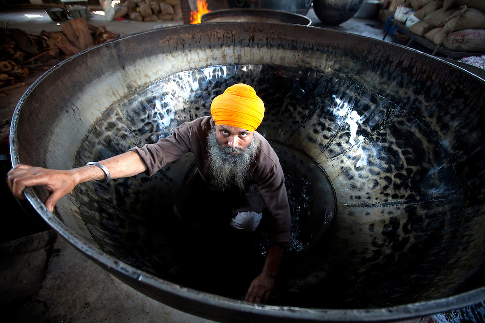 The amazing size of the pots in Sikh kitchens is demonstrated in this image. Here we see a cook in Golden temple cleaning a pot.The enormous pots are needed to cook for the tens of thousands of pilgrims who come everyday.