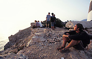 Group of teenagers sitting on rocky cliff top, over-looking the sea, 2000's