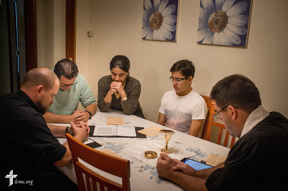 Jose Antonio (second from left) and his family, Sandra María and Juan José, celebrate the Eucharist led by the Rev. David Warner (right) and the Rev. Adam Lehman, LCMS career missionaries to Spain, at the family's home Friday, Nov. 4, 2016, in Valladolid, Spain. LCMS Communications/Erik M. Lunsford