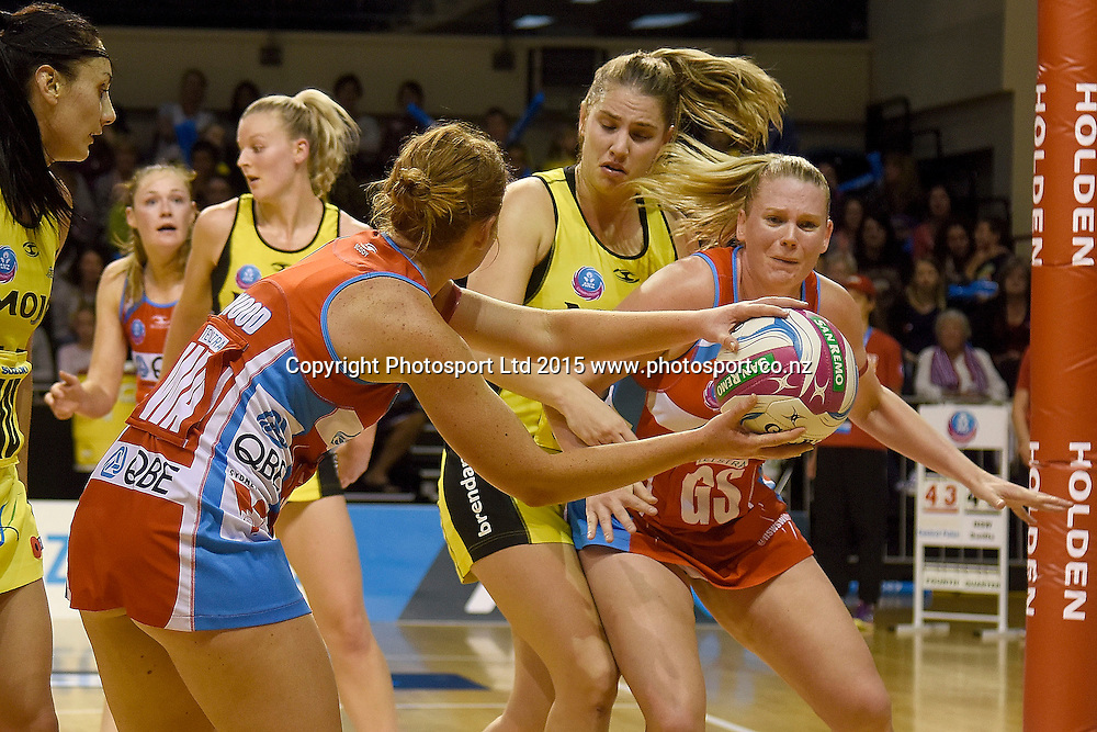 Swifts' Stephanie Wood (L) makes a pass to team mate Caitlin Thwaites (R with Pulse's Te Huinga Reo Selby-Rickit in defense during the ANZ Championship - Pulse v Swifts netball match at the TSB Arena in Wellington on Saturday the 25th of April 2015. Photo by Marty Melville / www.Photosport.co.nz