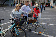Cyclists pass through Presernov Square with their dogs in the Slovenian capital, Ljubljana, on 25th June 2018, in Ljubljana, Slovenia. Ljubljana is a small city with flat terrain and a good cycling infrastructure. It was featured at eighth on the 'Copenhagenize' index listing the most bike-friendly cities in the world.