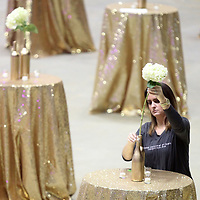 Ginger Montgomery, a Junior Auxiliary member, puts an arrangement together on a bar table during prepration for Friday nights Charity Ball at the BancorpSouth Arena.